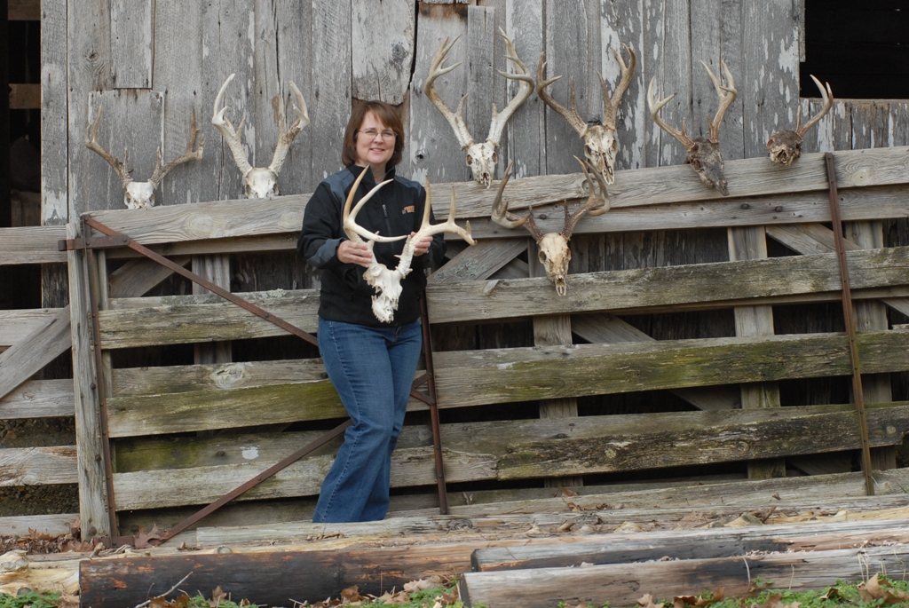 Seven whitetail buck skulls with anters and the woman who found them all