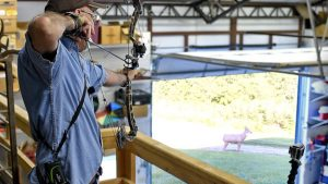 Grant practices with his bow from an elevated position.