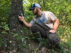 A hunter wears rubber boots when checking a Reconyx trail camera to help minimize scent