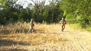 two young men broadcasting food plot seed