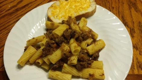Cubed venison and a pile of onions cooked down and served over pasta.