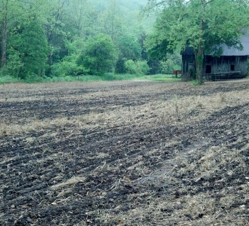 Open ground after planting with a barn in back ground