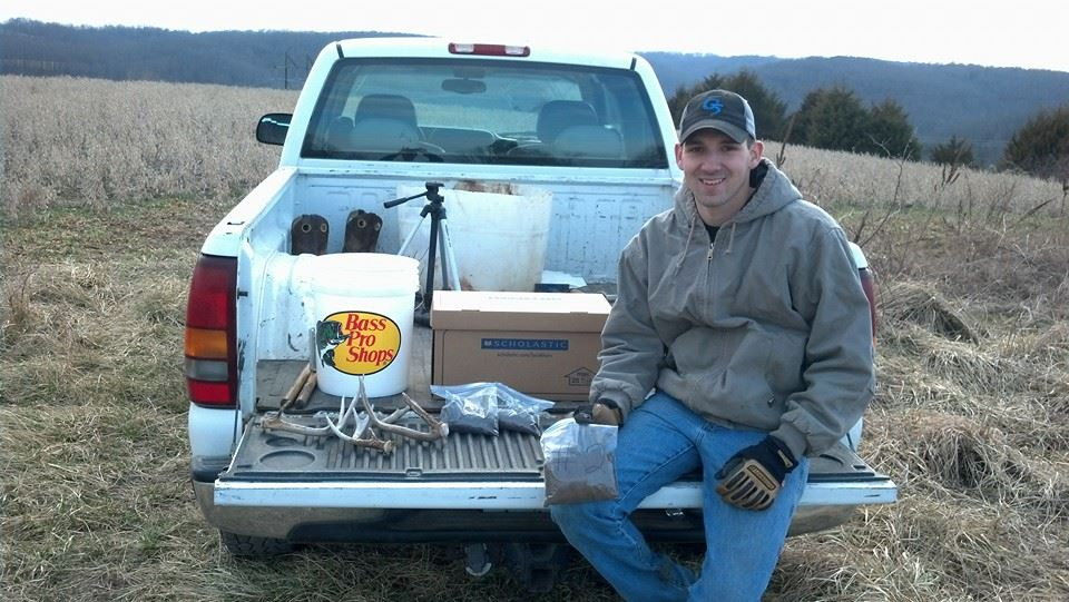 Brain sitting on truck tailgate with a bagged soil sample and shed antlers