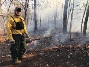 Tyler working a prescribed fire, holding a drip torch