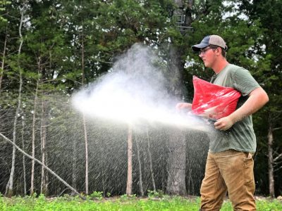 Owen Zimmer using a hand spreader to plant a food plot