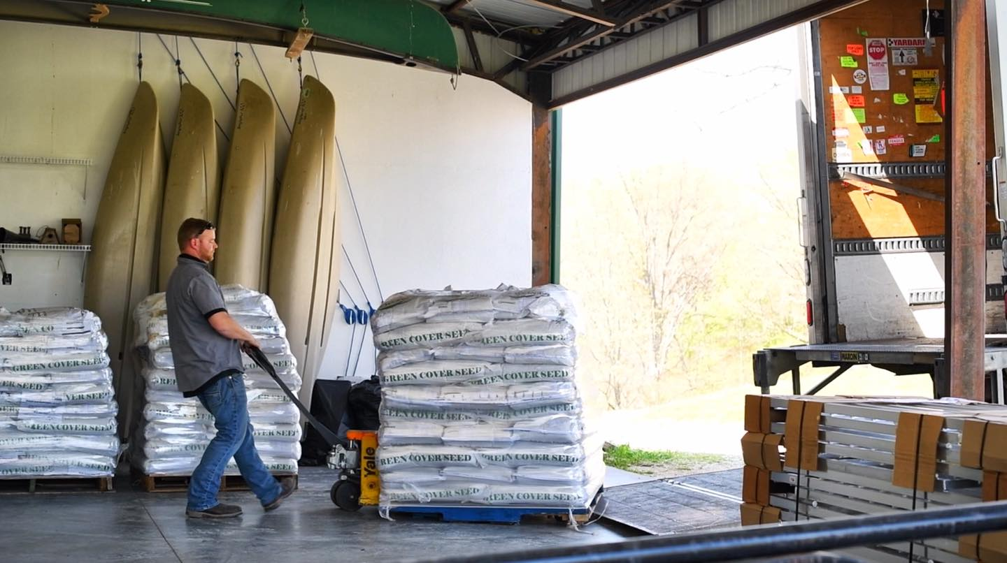 Pallet of green cover seed being unloaded from truck